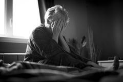 Müde ältere Frau auf ihrem Bett Stockfotografie