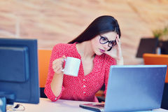 Müde überarbeitete Geschäftsfrau im Büro, das ihr Gesicht mit den Händen bedeckt Lizenzfreies Stockfoto