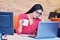 Müde überarbeitete Geschäftsfrau im Büro, das ihr Gesicht mit den Händen bedeckt Stockfotos