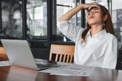 Müde überarbeitete junge asiatische Geschäftsfrau, die unter schwerer Krise an Arbeitsplatz leidet lizenzfreie stockfotos
