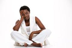 Müde afrikanische Frau, die mit den Beinen gekreuzt sitzt und Kopfschmerzen hat lizenzfreie stockbilder