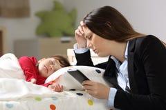 Müde Arbeitskraftmutter mit ihrem Tochterschlafen stockfotografie