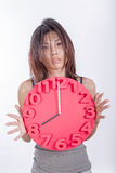 Müde Asiatin, die Uhr hält Stockbilder