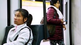 Müde asiatische Frau im weißen sportiven Hemd sitzt in beweglichem Zug und schaut herum stock video footage