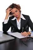 Müde betonte Geschäftsfrau, die an ihrem Schreibtisch arbeitet Lizenzfreie Stockfotos