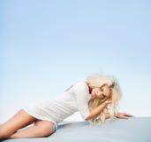 Müde blonde Dame, die aus den Grund liegt Stockfotografie