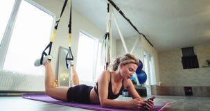 Müde blonde Dame nach Übungen eines ausdehnenden Körpers mit Gummibändern hat sie eine entspannende Zeit plaudernd auf ihr