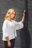 Müde blonde rührende schwarze Wand der Geschäftsfrau draußen Lizenzfreie Stockbilder
