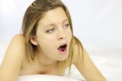 Müde blonde Schönheit, die im Bett gähnt Lizenzfreie Stockfotografie
