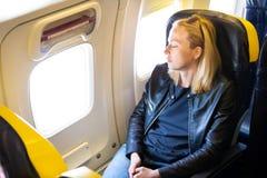 Müde blonde zufällige kaukasische Dame, die auf Sitz beim Reisen mit dem Flugzeug Nickerchen macht Stockfotos