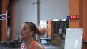 Müde Eignungsfrau, die doppeltes Training des springenden Seils in der Turnhalle tut stock video footage