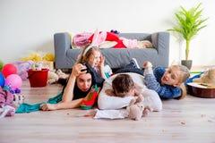 Müde Eltern und herumtollende Kinder stockfotos