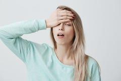 Müde erschöpfte blonde junge Frau hat schreckliche Kopfschmerzen nach der Arbeit, kommt nach Hause in schlechte Stimmung und oben Lizenzfreies Stockfoto