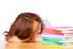 Müde faule Asiatin, die nahe Stapel Büchern schläft Stockfotos