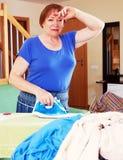 Müde Frau bügelt Kleidung lizenzfreie stockfotos