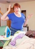 Müde Frau bügelt Kleidung Lizenzfreie Stockfotografie
