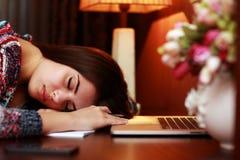 Müde Frau, die auf dem Tisch schläft Lizenzfreie Stockbilder