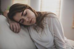 Müde Frau, die auf die Couch einschläft lizenzfreies stockbild
