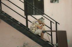 Müde Frau, die auf Treppe nachdem dem Fegen sitzt lizenzfreie stockbilder