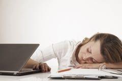 Müde Frau, die bei der übermäßigen Arbeit des Arbeitsplatzes schläft, Überlastung, Stockfotografie