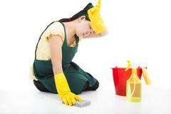 Müde Frau, die den Boden säubert stockfotos