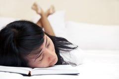 Müde Frau, die ein Buch liest Stockfotos
