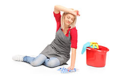 Müde Frau, die einen Fußboden säubert Stockbild