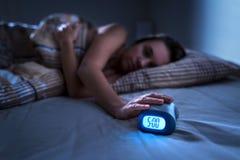 Müde Frau, die früh für Arbeit oder Schule morgens aufwacht Mürrischer Damendruck dösen Knopf oder, drehend weg vom Wecker lizenzfreie stockfotografie