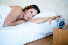 müde Frau, die heraus erreicht, um ihre Warnung abzustellen Stockfoto