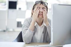 Müde Frau, die ihre Augen berührt