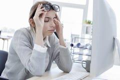 Müde Frau, die ihre Augen berührt stockfotos