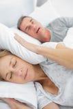 Müde Frau, die ihre Ohren von den Geräuschen des Ehemanns schnarchend blockiert Stockbilder