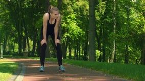 Müde Frau, die nachdem am Park stark laufen stillsteht Geeignetes Mädchen entspannen sich, nachdem sie gerüttelt hat stock footage