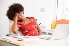Müde Frau, die am Schreibtisch im Design-Studio arbeitet Stockfotos