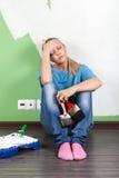 Müde Frau mit Farbenwerkzeugen Stockfoto