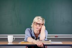 Müde Frau am Schreibtisch im Klassenzimmer Stockbild