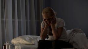 Müde Frau von mittlerem Alter, die auf Bett nachts, Schlaflosigkeitskrankheit, Problem sitzt stockbild