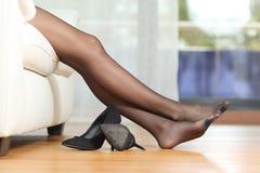 Müde Frauenbeine, die auf Couch stillstehen stockfoto