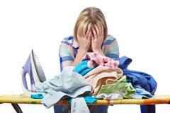 Müde Frauenhausfrau bügelte die lokalisierte Kleidung Stockfotografie