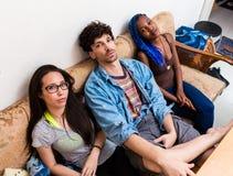 Müde Freunde, die auf Sofa sitzen lizenzfreies stockbild