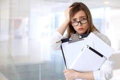 Müde Geschäftsfrau bei der Stellung im Büro Stockfotos
