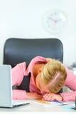 Müde Geschäftsfrau, die auf Büroschreibtisch schläft Lizenzfreie Stockfotografie