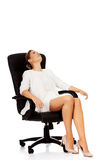 Müde Geschäftsfrau, die auf Lehnsessel sitzt stockfotografie