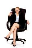 Müde Geschäftsfrau, die auf Rollstuhl mit Tasse Kaffee sitzt Lizenzfreies Stockbild