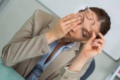 Müde Geschäftsfrau, die enorme Kopfschmerzen hat lizenzfreie stockfotografie