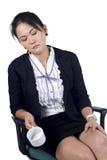 Müde Geschäftsfrau, die in ihrem Stuhl schläft und leeres cof anhält Lizenzfreie Stockbilder