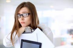 Müde Geschäftsfrau, die im Büro steht Lizenzfreies Stockfoto