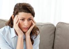 Müde Geschäftsfrau, die Kopfschmerzen auf dem Sofa hat lizenzfreies stockbild