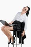 Müde Geschäftsfrau, die mit einem Laptop sitzt Weiß lokalisiertes backg Lizenzfreie Stockfotos