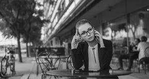 Müde Geschäftsfrau, die am Mobiltelefon, Schwarzweiss spricht Stockbild